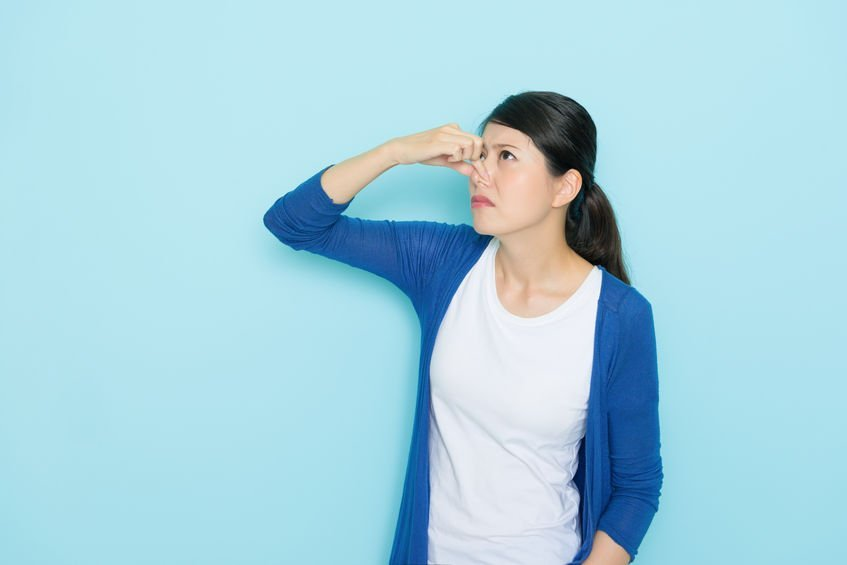 woman smelling bad paint using hands closing nose